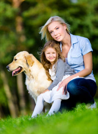 Mother and daughter with golden retriever sitting on the grass at the summer park photo