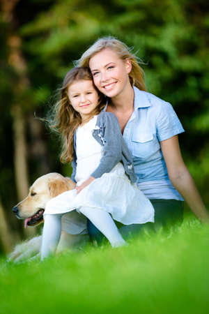 Mother and daughter with labrador sitting on the grass at the summer park photo