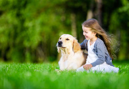 golden retriever: Little girl sitting on the grass with dog in the summer park Stock Photo