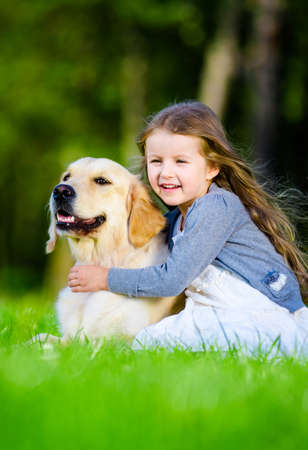 Little girl sitting on the grass with labrador in the summer park Stock Photo