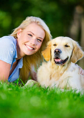 Woman with golden retriever lying on the green grass in the park, close up