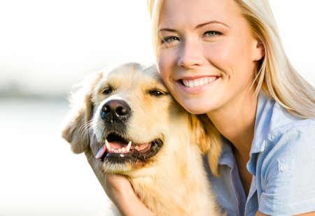 Nahaufnahme von blonden Frau umarmt Golden Retriever Standard-Bild - 22528440