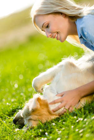 Close up of woman who strokes golden retriever lying on the green grass in the park photo