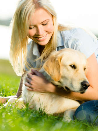 Portrait of blond girl with labrador retriever lying on grass photo