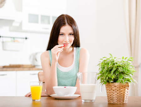 Portrait of the girl eating healthy muesli with milk and strawberry and orange juice sitting at the kitchen table