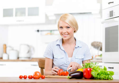 Woman chops vegetables for salad sitting at the kitchen table Stock Photo - 22528500