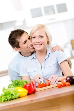 Man kisses young girl while she is cooking sitting at the kitchen table full of groceries photo