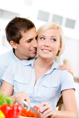 Man kisses woman while she is cooking sitting at the kitchen table full of groceries Stock Photo - 22528501