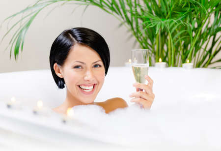 Woman taking a bath with suds drinks alcohol and relaxes