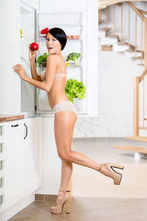 Full length of woman near the opened refrigerator full of vegetables and fruit. Concept of healthy and dieting food photo