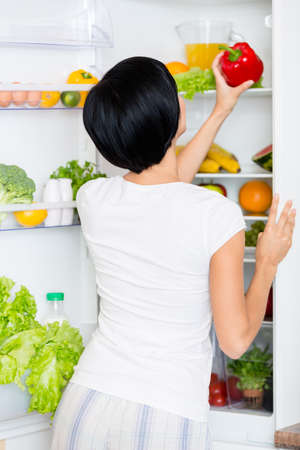 takes: Woman takes red pepper from the opened refrigerator full of vegetables and fruit. Concept of healthy and dieting food