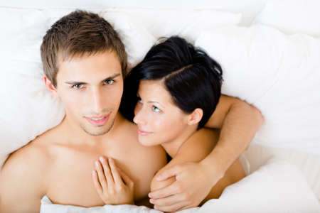 Close up view of couple lying in bedroom, top view. Concept of love and affection photo