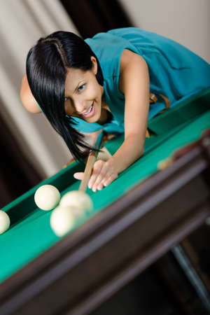 Woman playing billiard. Spending free time on gambling photo