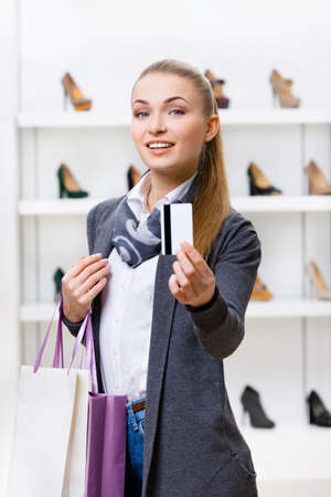 Lady showing credit card in footwear shop with great variety of stylish shoes photo