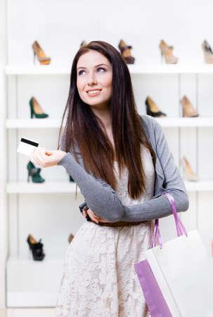comprando zapatos: Manos femeninas de tarjeta de crédito en la tienda de calzado con una gran variedad de zapatos con estilo