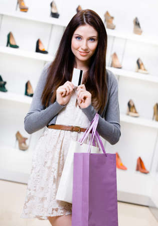 Girl hands credit card in footwear shop with great variety of stylish shoes photo