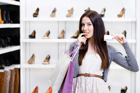 Girl keeps credit card in footwear shop with great variety of stylish shoes photo