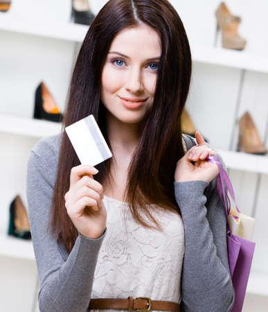 comprando zapatos: Mujer tiene tarjeta de crédito en la tienda de calzado con una gran variedad de zapatos con estilo