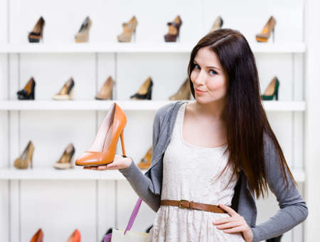 Half-length portrait of woman keeping brown leather shoe in shopping center