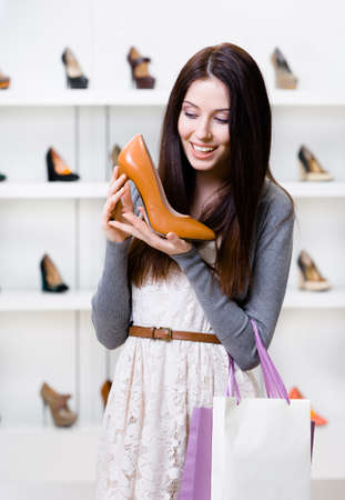 Half-length portrait of woman keeping brown leather heeled shoe in shopping center photo