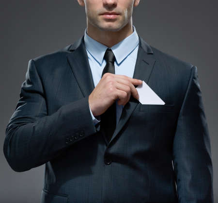 white body suit: Part of body of man who takes out white card from the pocket of business suit, copyspace Stock Photo