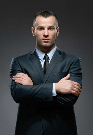 half body: Half-length portrait of man wearing business suit and black tie with crossed arms Stock Photo