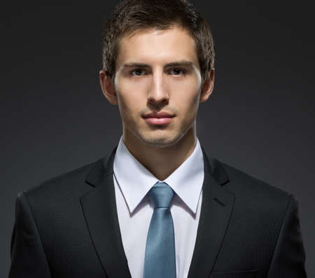 professionalism: Front view of self-confident business man in dark suit with tie. Concept of professionalism and success in business