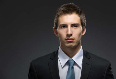 professionalism: Front view of self-confident business man in dark suit with black tie. Concept of professionalism and success in business Stock Photo