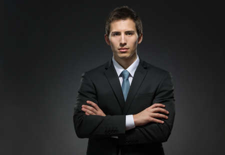 professionalism: Half-length portrait of business man with his crossed arms. Concept of professionalism and business success