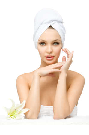 Woman with towel on head touches face sitting near a white lily, isolated on white. Concept of healthcare, beauty and youth photo