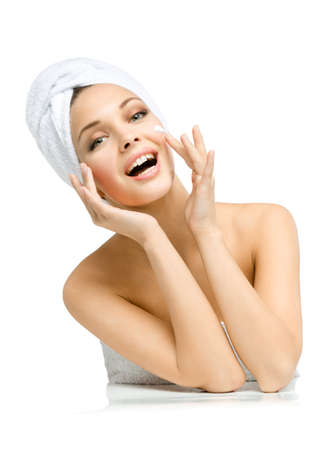 Woman with towel on head applies cream on face, isolated on white. Concept of healthcare, beauty and youth photo