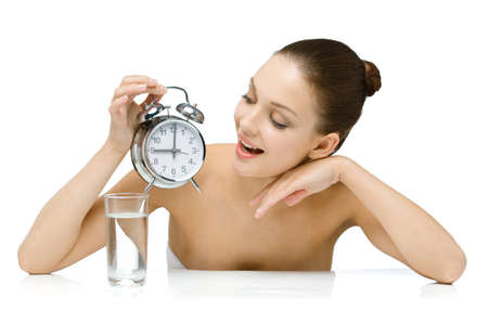 Naked girl with glass of water hands alarm clock and looks at it, isolated on white photo