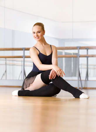 Ballerina does exercises sitting on the wooden floor in the classroom with barre and mirrors photo