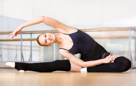 Bending female ballet dancer stretches herself on the floor in the classroom Stock Photo