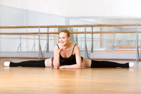 Ballerina does the splits sitting on the floor in the studio with barre and mirrors photo