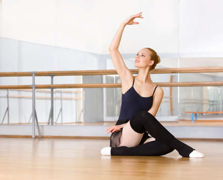 barre: Ballerina works out sitting on the floor in the classroom with barre and mirrors