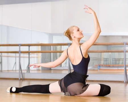 barre: Ballerina does exercises sitting on the floor in the classroom with barre and mirrors Stock Photo