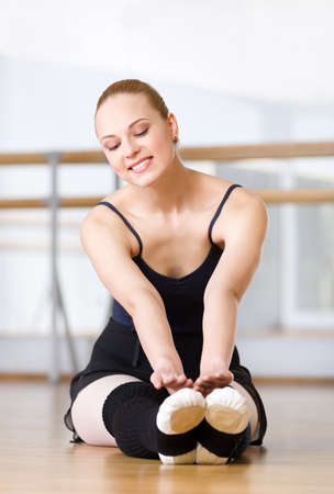 warmers: Ballerina stretches herself on the wooden floor in the classroom