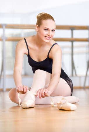 barre: Sitting on the floor ballerina laces the ribbons of the pointes