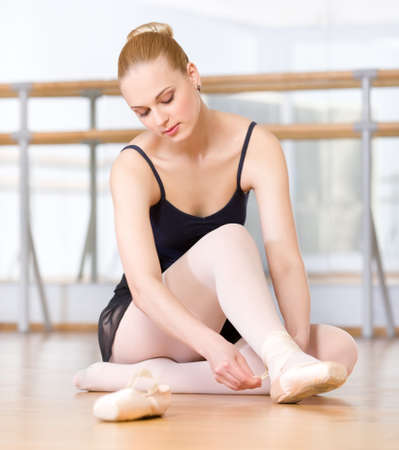 pointes: Sitting on the wooden floor ballerina laces the ribbons of the pointes