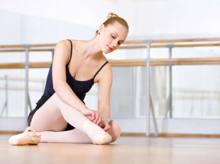 Sitting on the floor ballet dancer laces the ribbons of the pointes