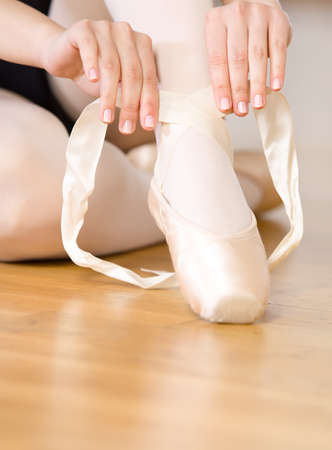 pointe: Close up view of legs of sitting on the floor ballerina who laces the ribbons of the pointes