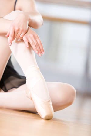 Close up view of legs of sitting on the floor ballerina who wears white pointes photo