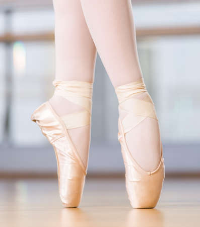 barre: Close-up view of dancing legs of ballerina wearing white pointes in the dancing hall