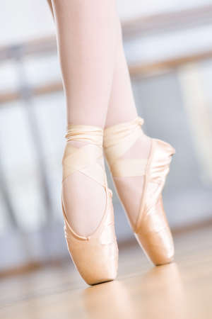 Close up shot of dancing legs of ballerina wearing white pointes in the dancing hall