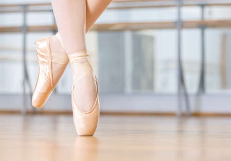 work shoes: Closeup of dancing legs of ballerina wearing white pointes in the dancing hall Stock Photo
