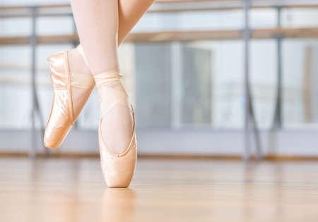 Closeup of dancing legs of ballerina wearing white pointes in the dancing hall Standard-Bild