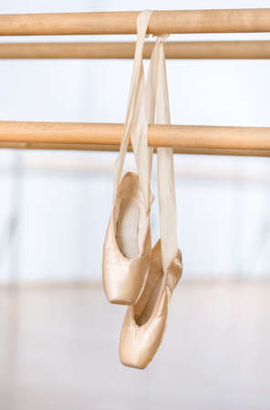 Close up view of pointes for ballet on barre near the mirrors in classroom