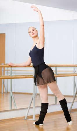 Tragen Trikot und Stulpen Ballett-Tänzerin tanzt in der Nähe barre und Spiegel in Tanzsaal Lizenzfreie Bilder