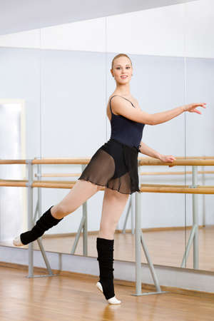 barre: Wearing leotard and warmers athlete dances near barre and mirrors in dancing hall